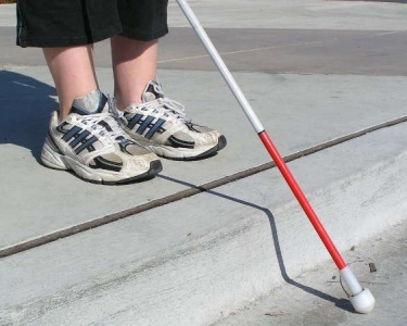Blind woman traveling with white cane