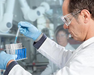 A Professor extracts a blue Liquid probe from a filled test tube.